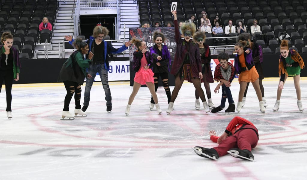 Intermediate Thriller skaters laughing at boy lying on ice.