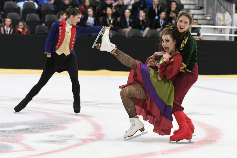 Senior skater holding another skater in a dress who is falling in their arms.