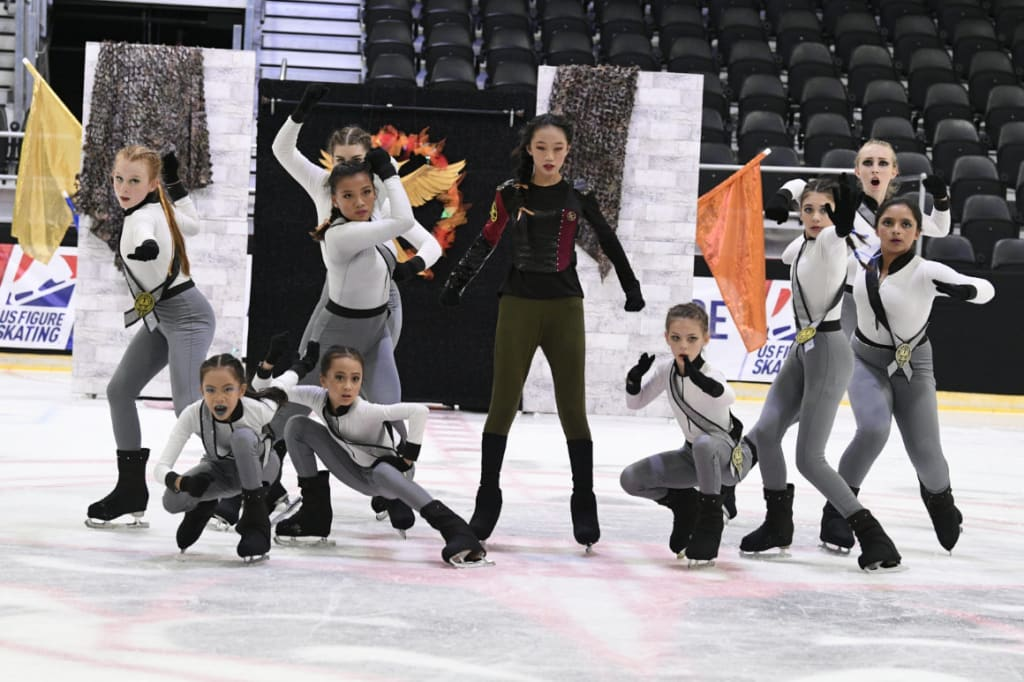 Novice Team on ice in champion and combat poses.
