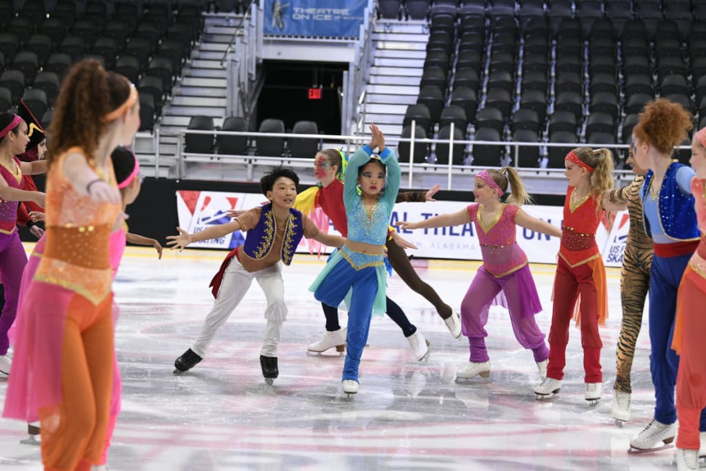 Preliminary skaters dressed in Aladdin costumes with Jasmin and Aladdin skating in between rows of skaters