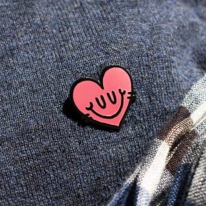 Pin's émaillé en forme de cœur rose vu sur sa carte, seul et de dos, avec une inscription au dos