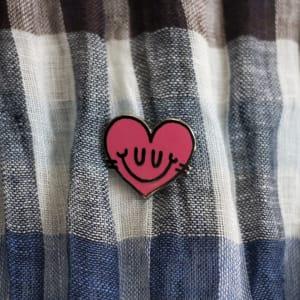Pin's émaillé cœur rose sur une étoffe à carreaux bleus, marrons et blancs