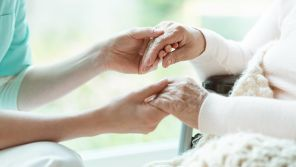 nurse holding elderly patients hands