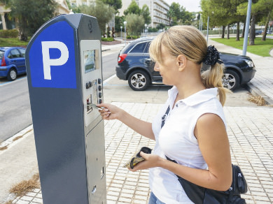 image of a woman using a parking meter