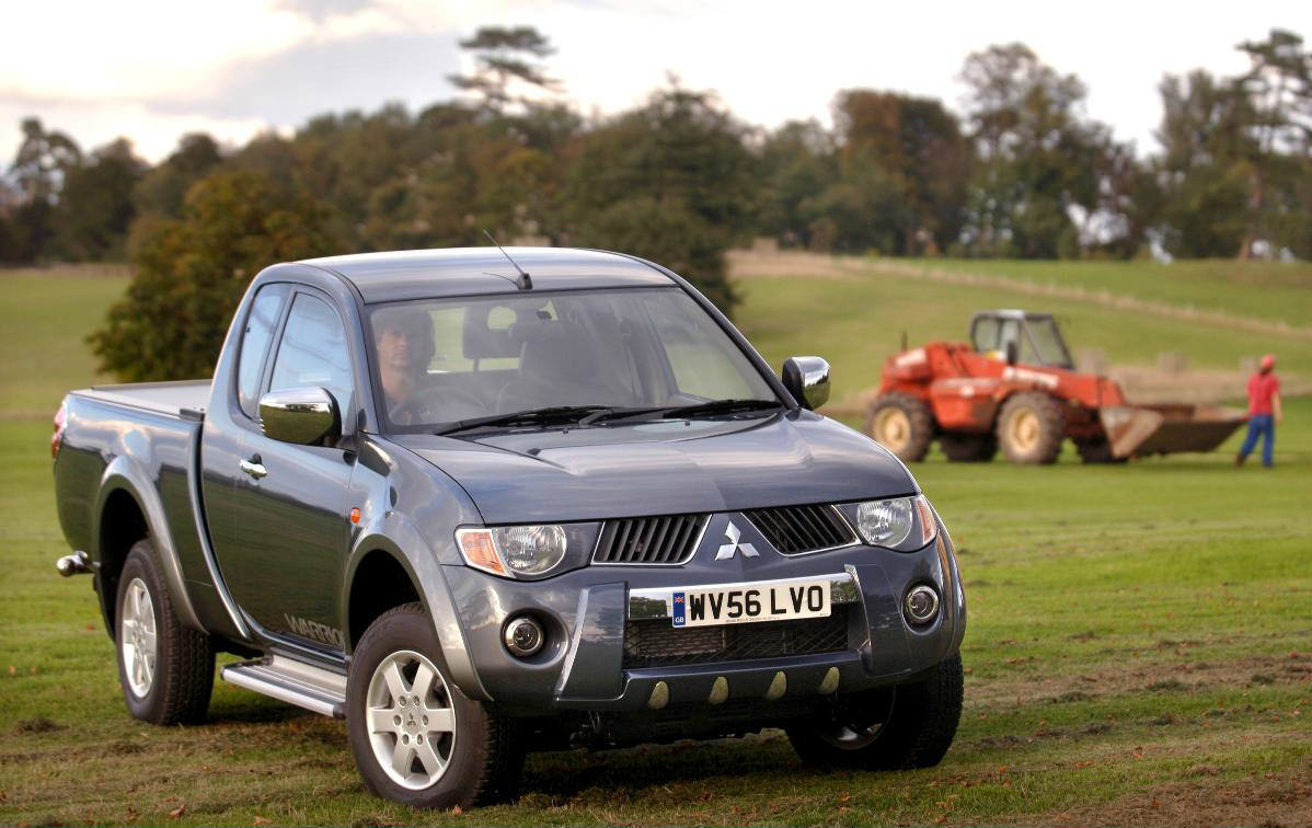 image of a blue mitsubishi l200 car in a field
