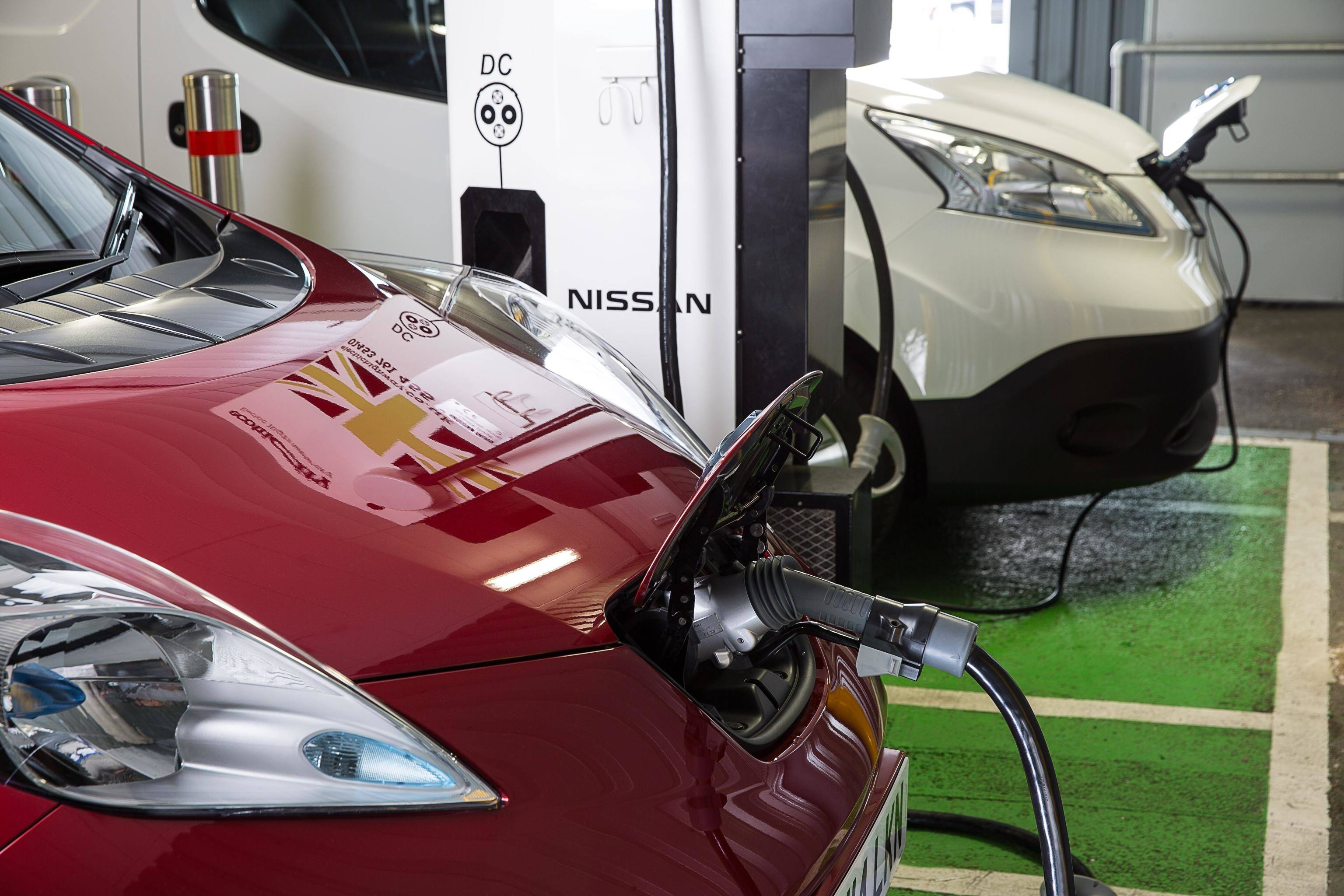 image of two nissan leaf cars plugged into charging stations