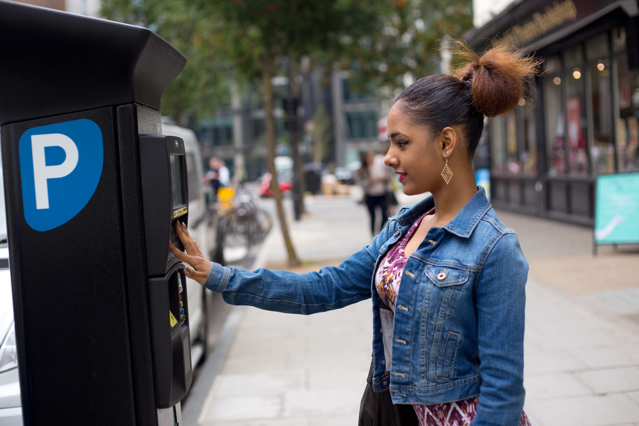 image of a person purchasing a parking ticket from a machine