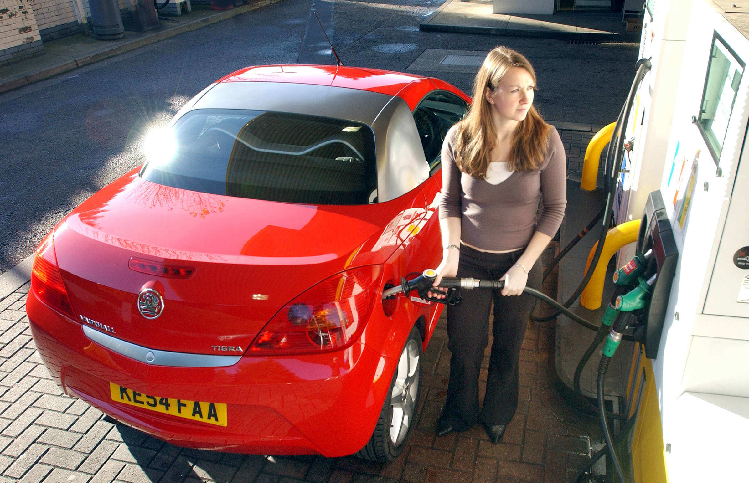 image of a person filling up their car at a petrol station