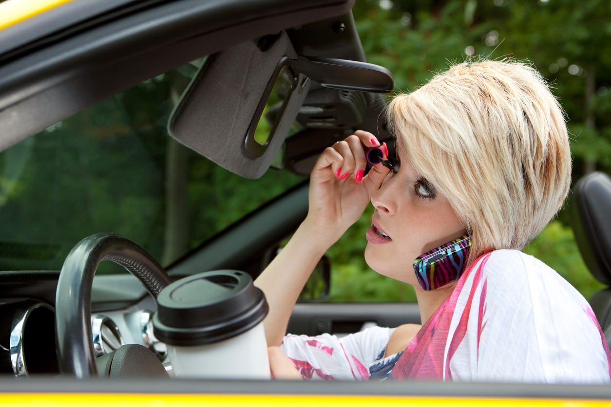 image of a person distracted from driving with makeup and phone