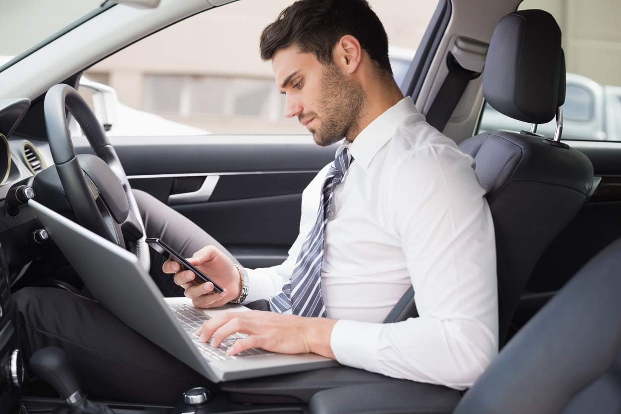 image of a person distracted from driving with computer and phone