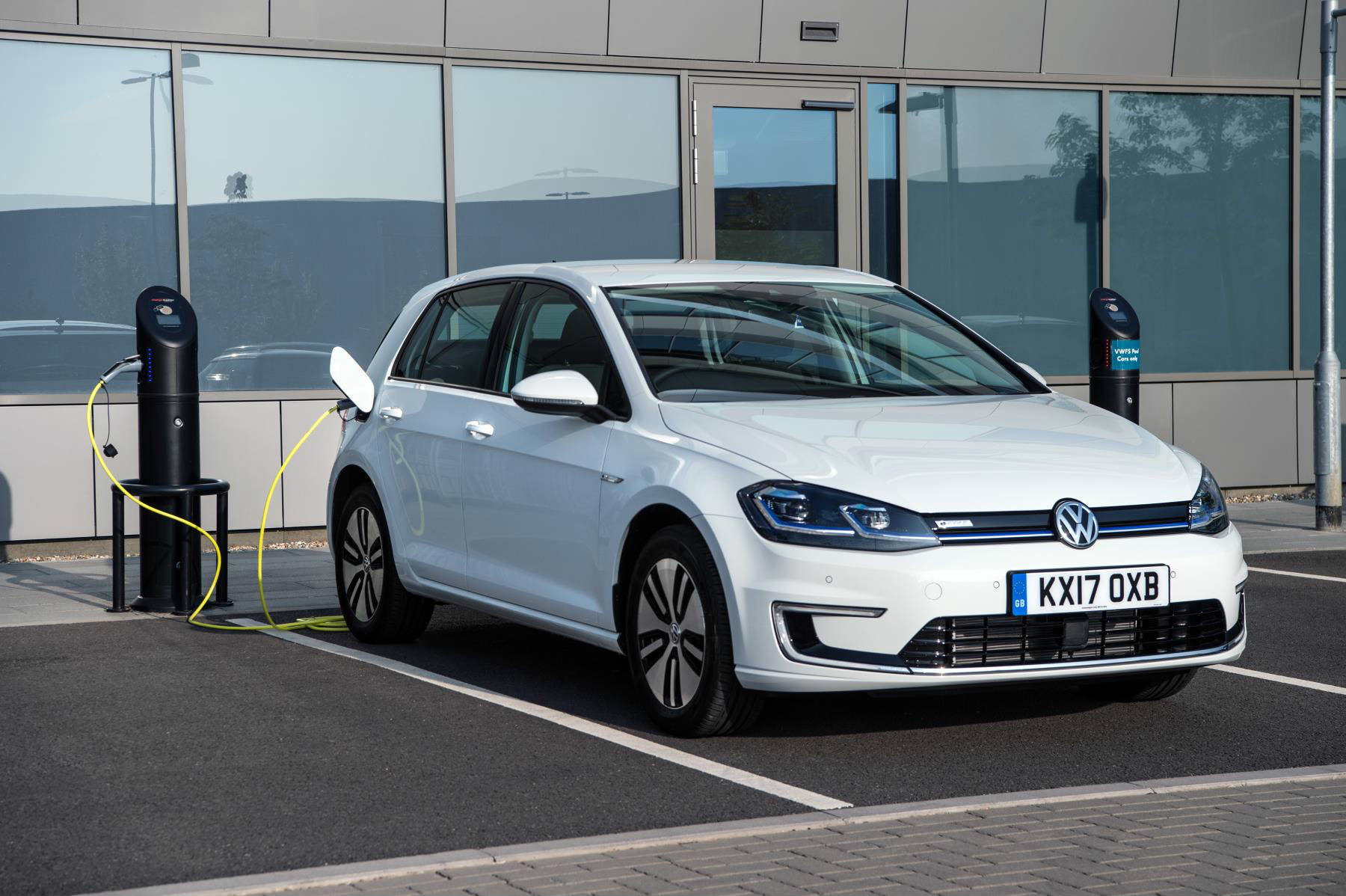 image of a white electric volkswagen golf car plugged into a charging point