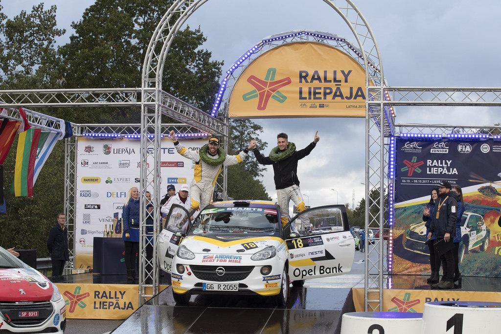 image of chris ingram celebrating on top of his rally car