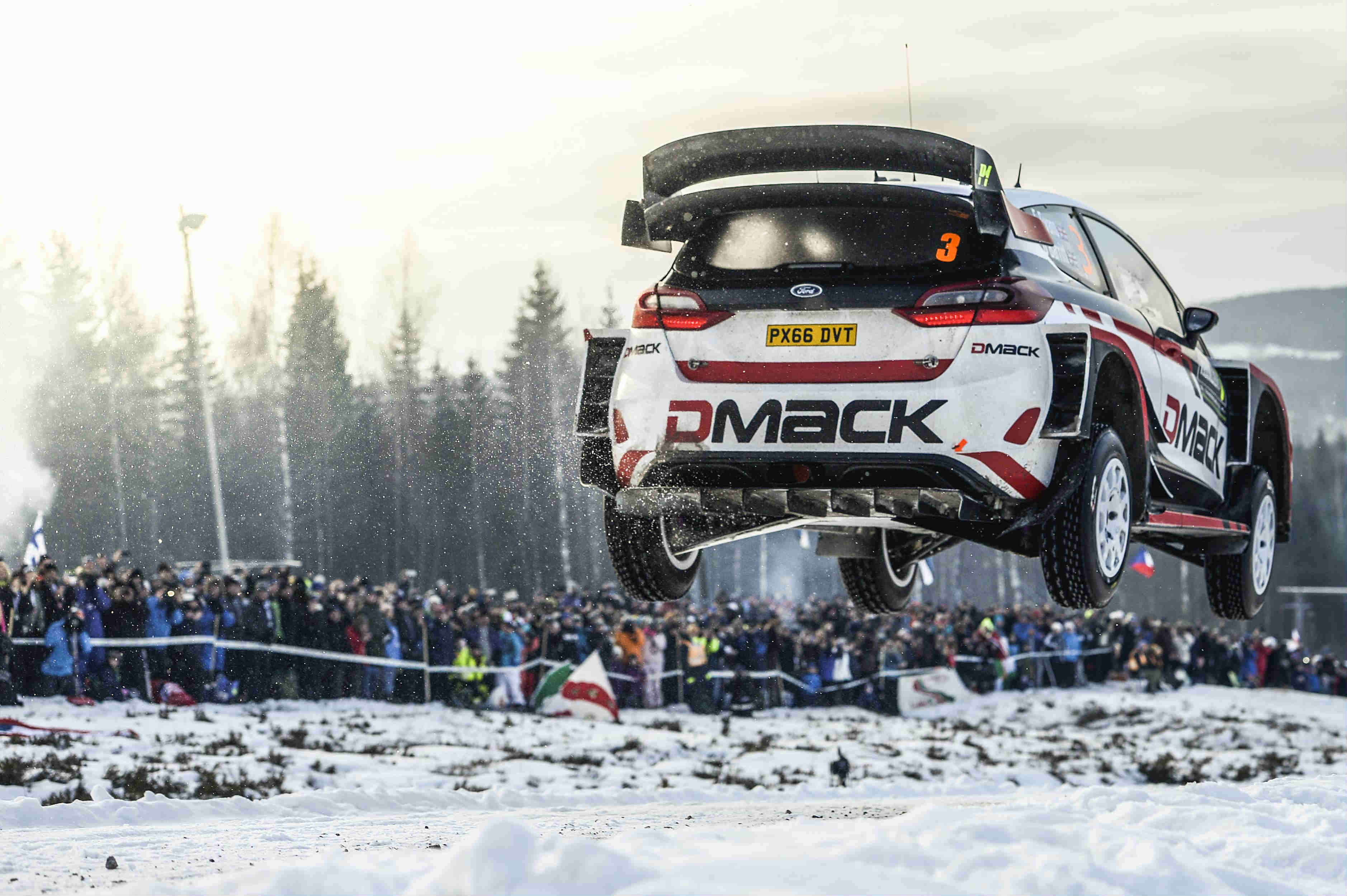image of elfyn evans rally car in mid air during a snow race