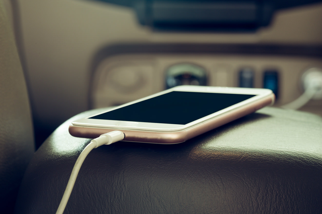 image of a smart phone charging in a car