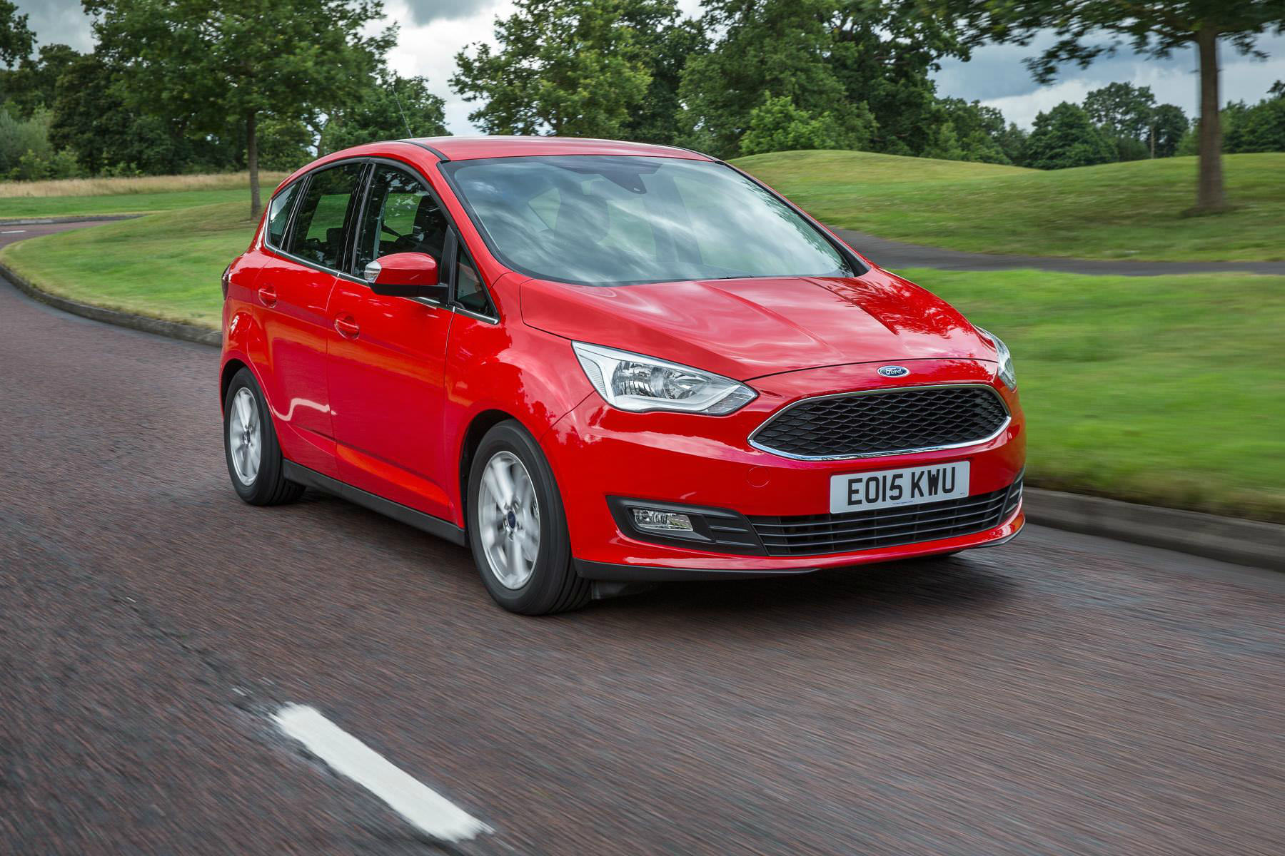image of a red ford c max car on a city road