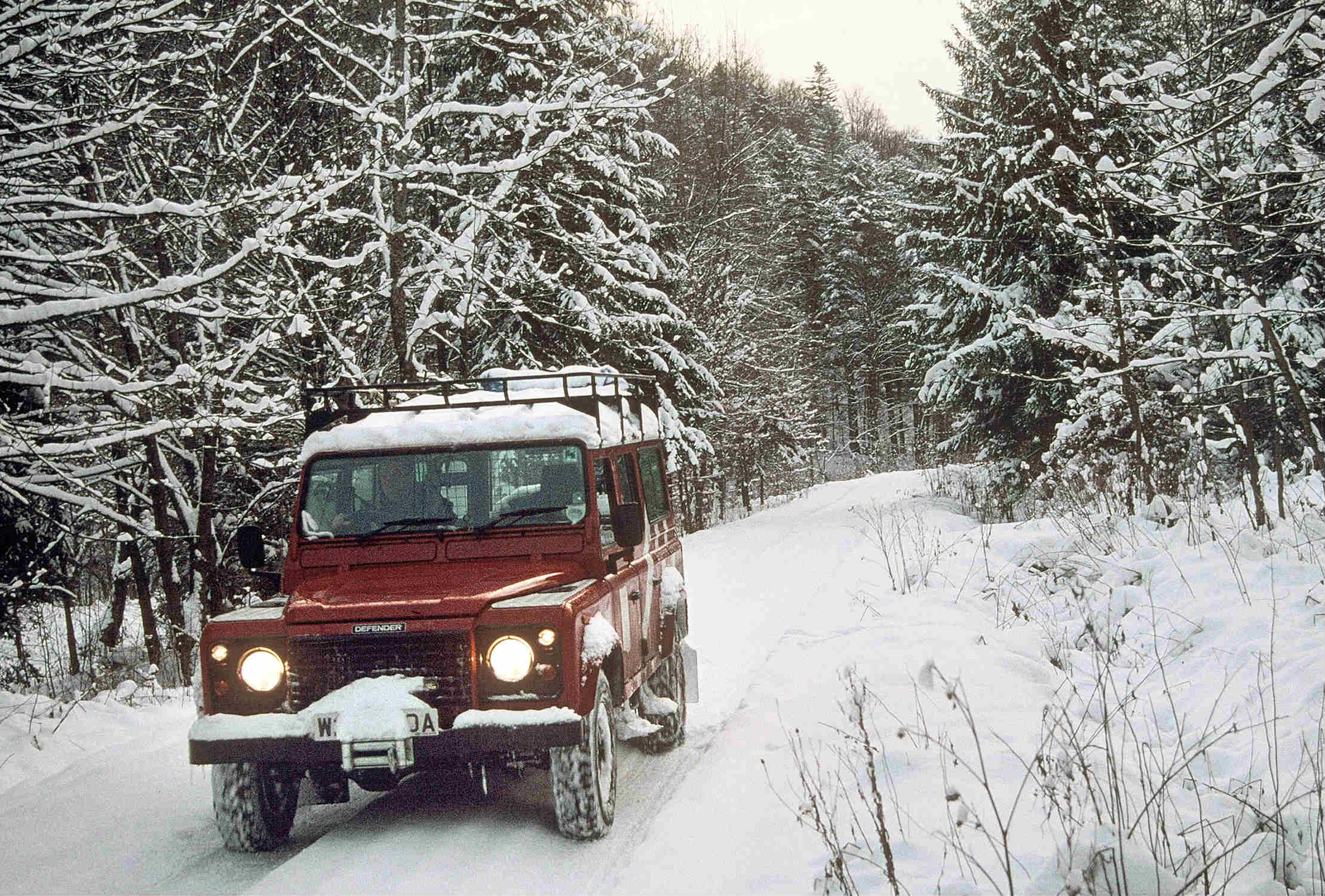 image of a vintage land rover in snow conditions