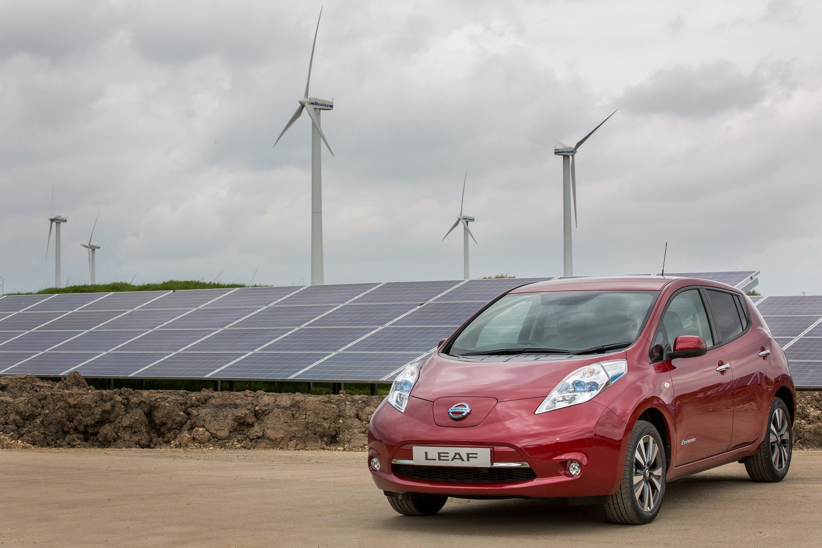image of a red nissan leaf electric car parked next to solar panels
