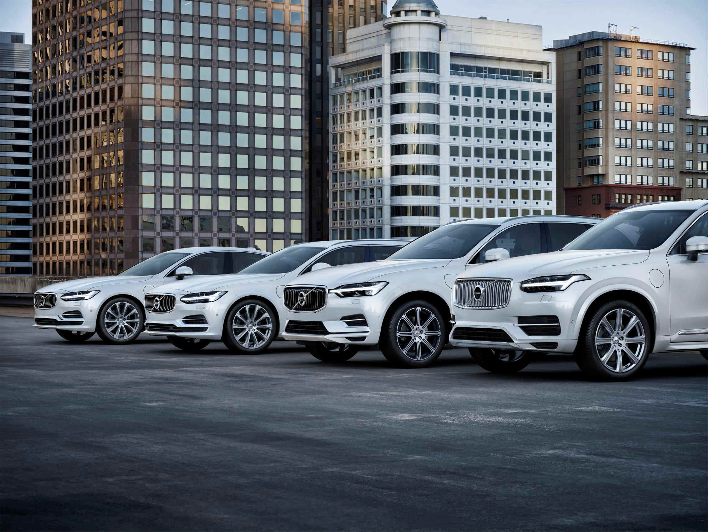 image of a range of white volvo cars parked on top floor of a multi storey car park