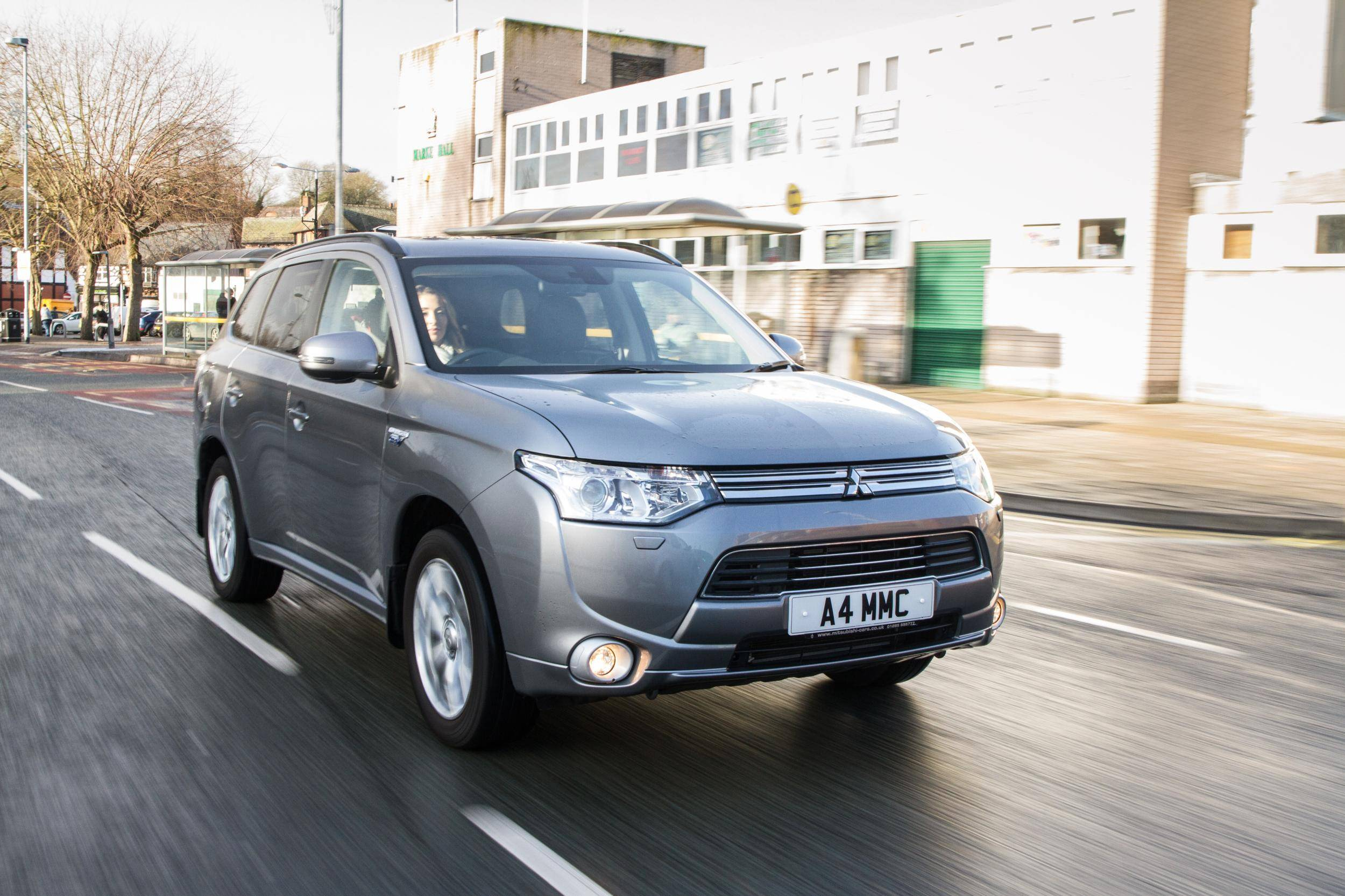 Woman Driving a Grey Hybrid SUV Mitsubishi PHEV down a road