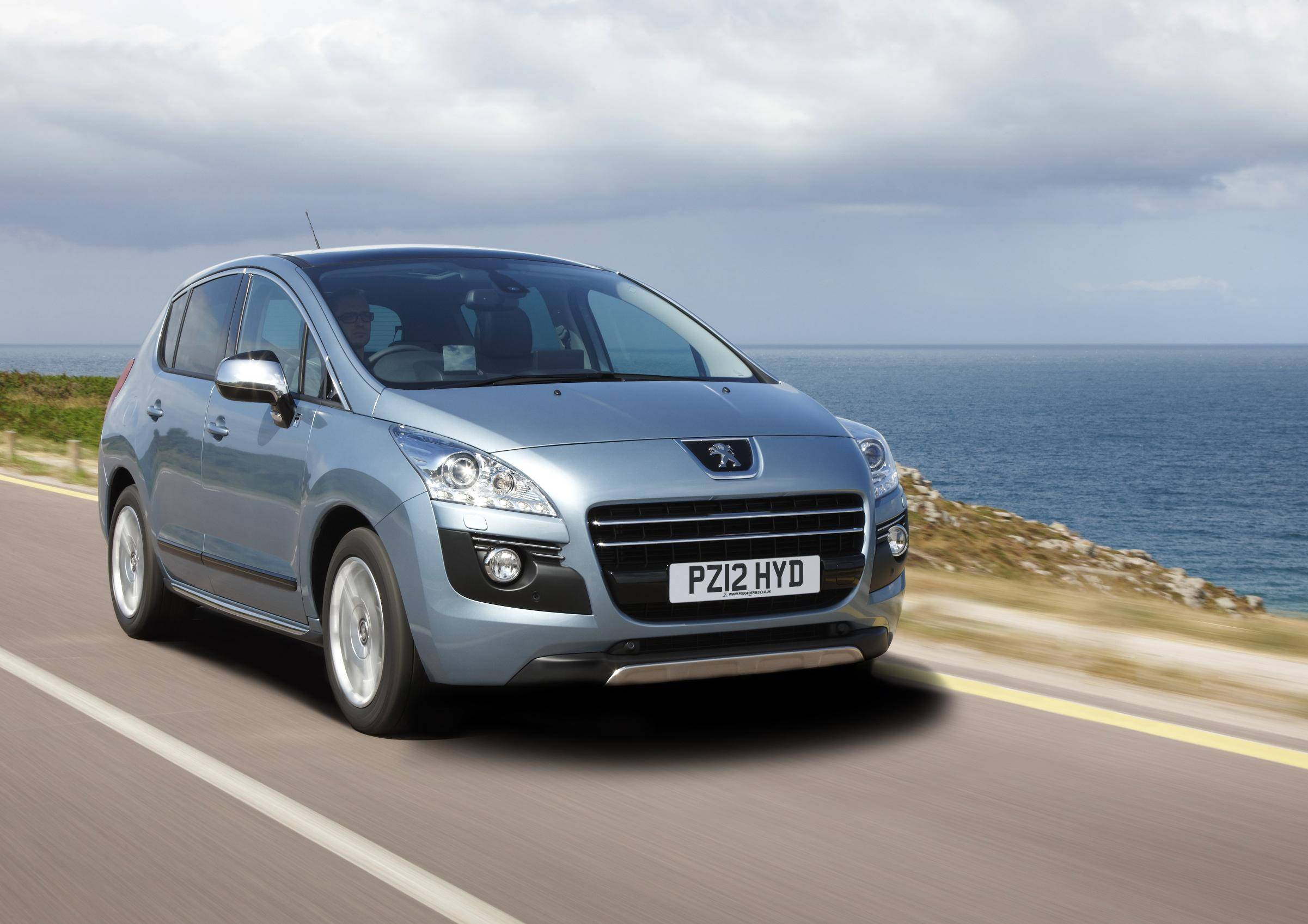 Man driving a Grey Hybrid SUVs Peugeot 3008 near the sea