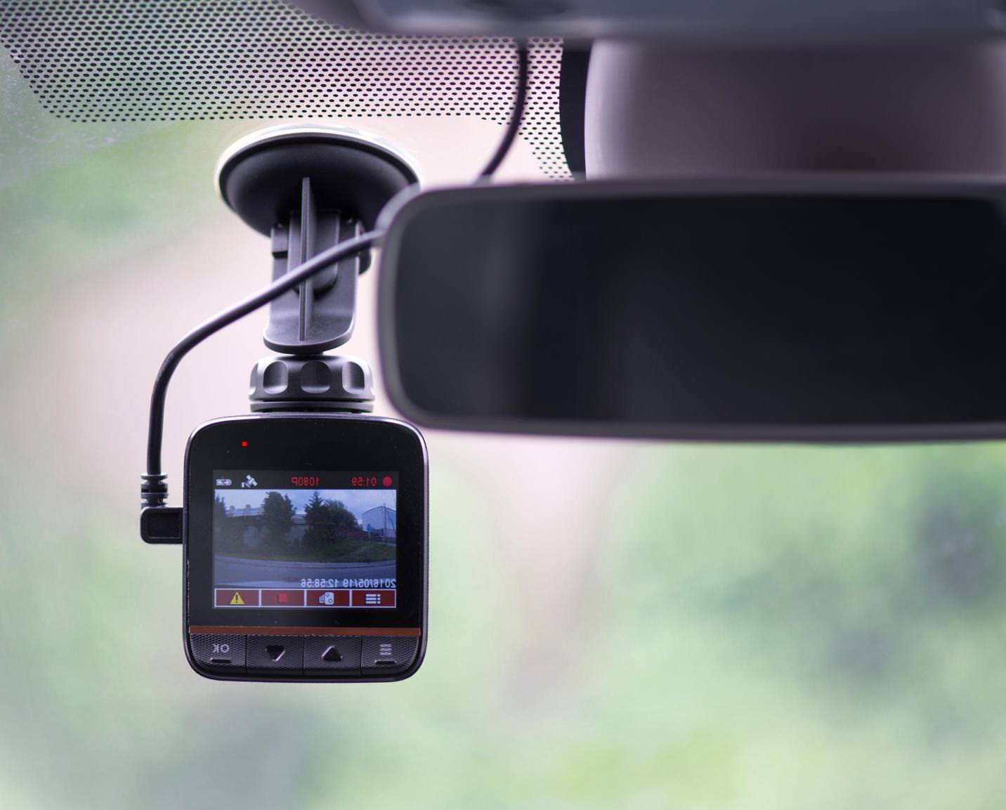 A dash cam with a monitor attached to a car windscreen recording the road