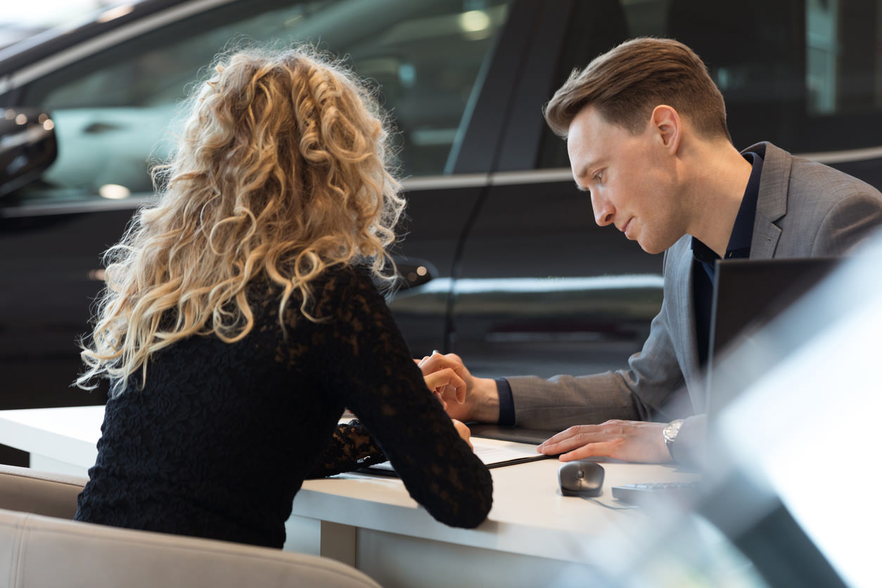 A woman and a man overlooking details on a document in a dealership