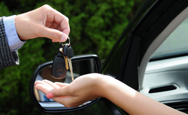 A man handing a set of car keys over to a new car owner