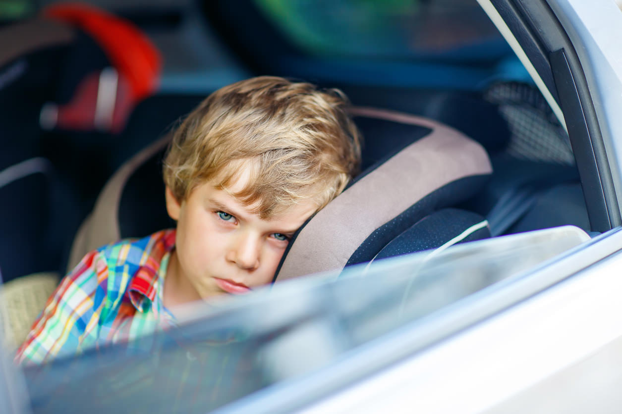 Unwell child seated on a booster seat staring outside of a car window.