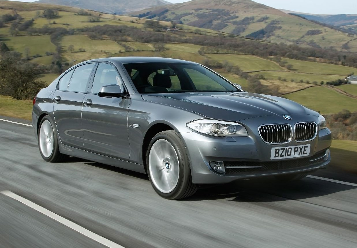 Grey BMW 5-Series driving through countryside