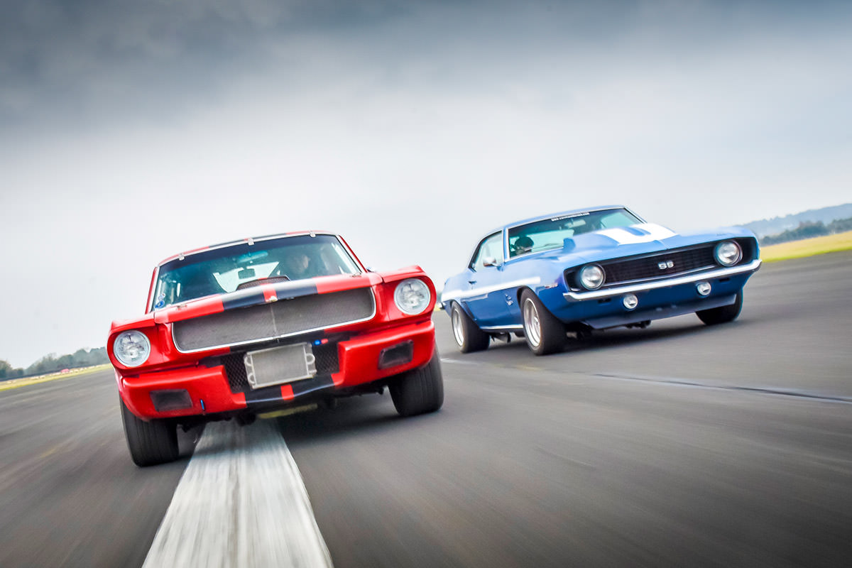 image of two ford mustang cars side by side on a road