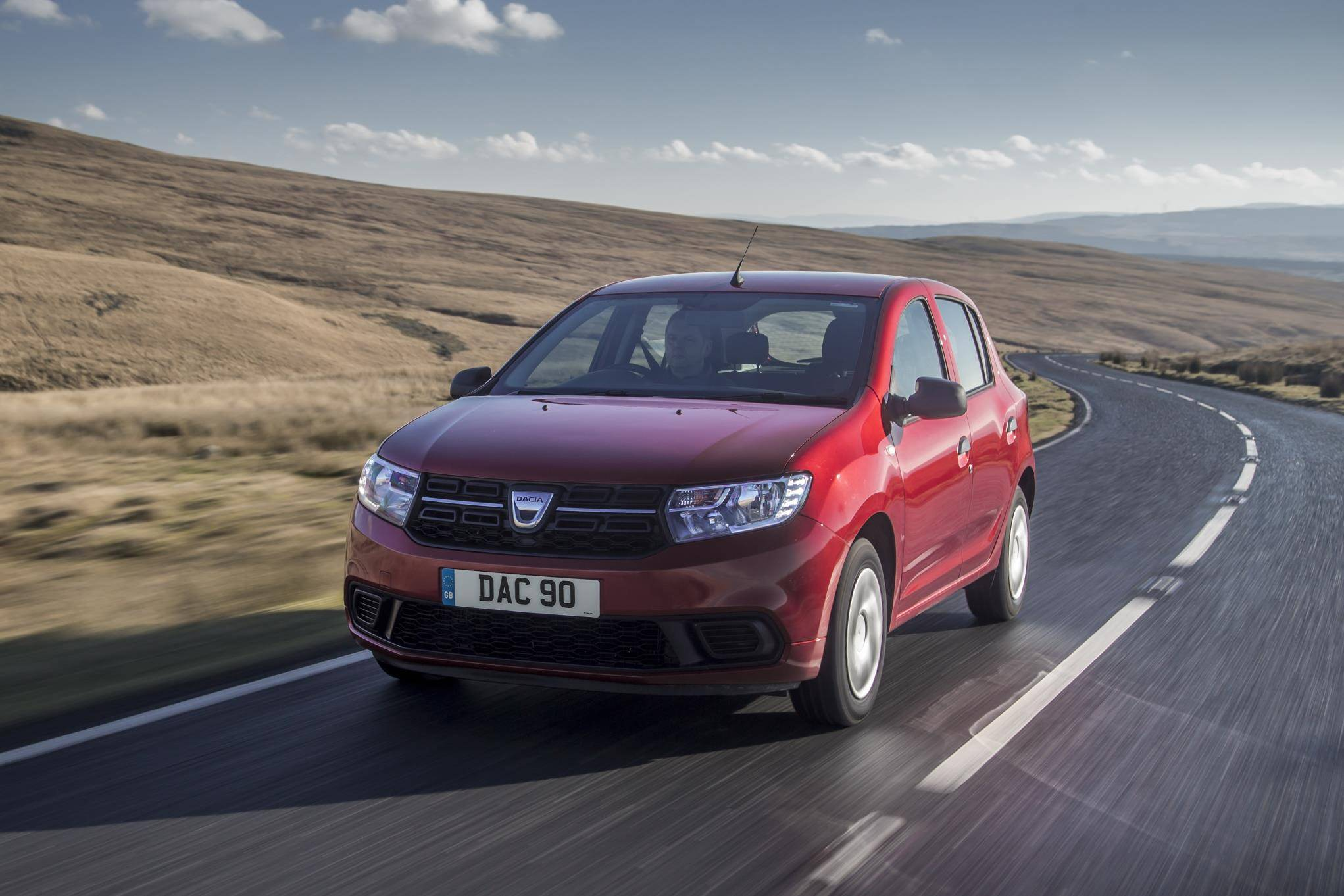 Red Renault Sandero driving along a country lane