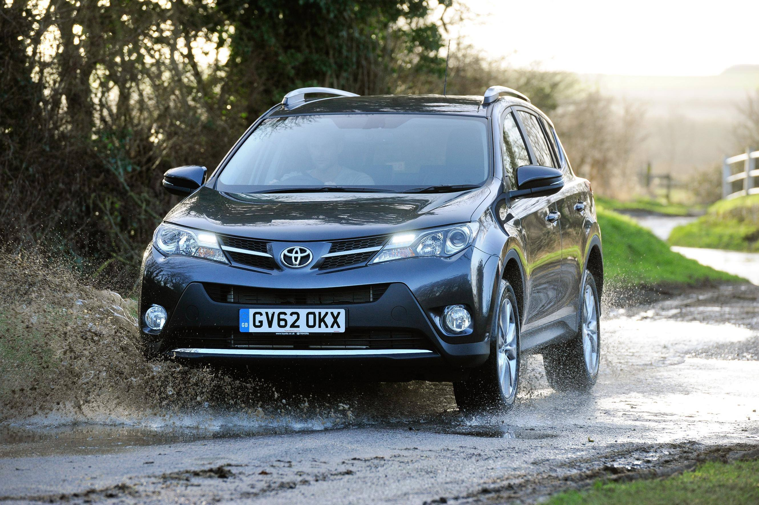 image of a black toyota rav4 car drivng through a puddle