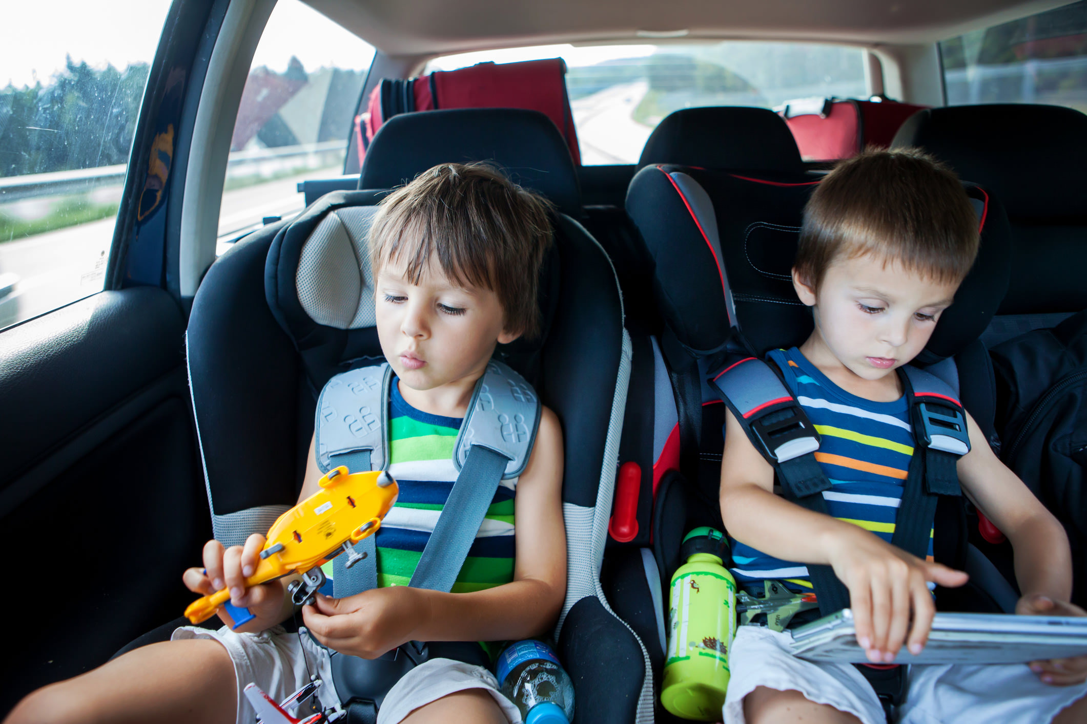 Two kids playing with toys. essential accessories to pack in a car for a road trip