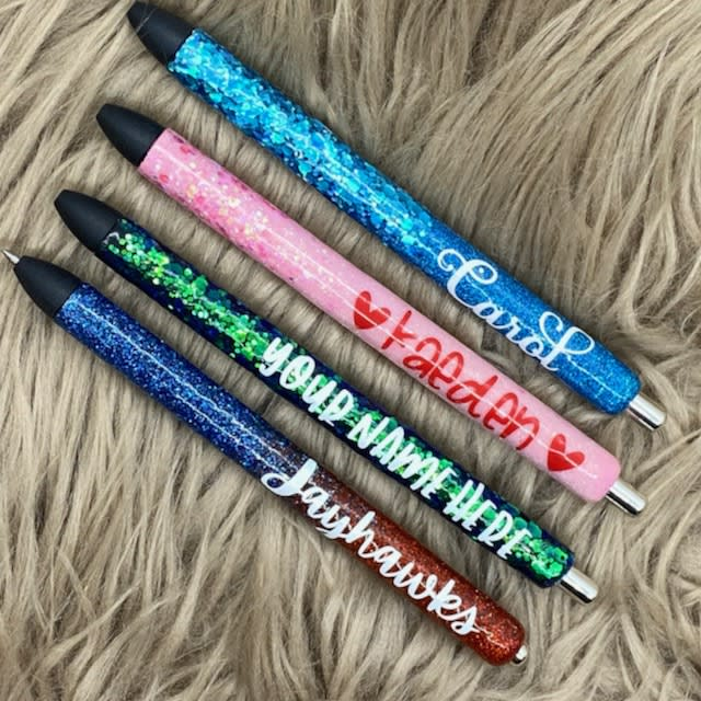 Four glitter pens personalized with names.