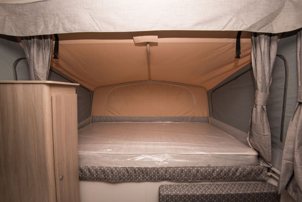 Both beds are innerspring mattresses with privacy curtains, zippered canvas windows and mesh screens. (image credit: Brendan Batty/campertrailerreview.com.au)