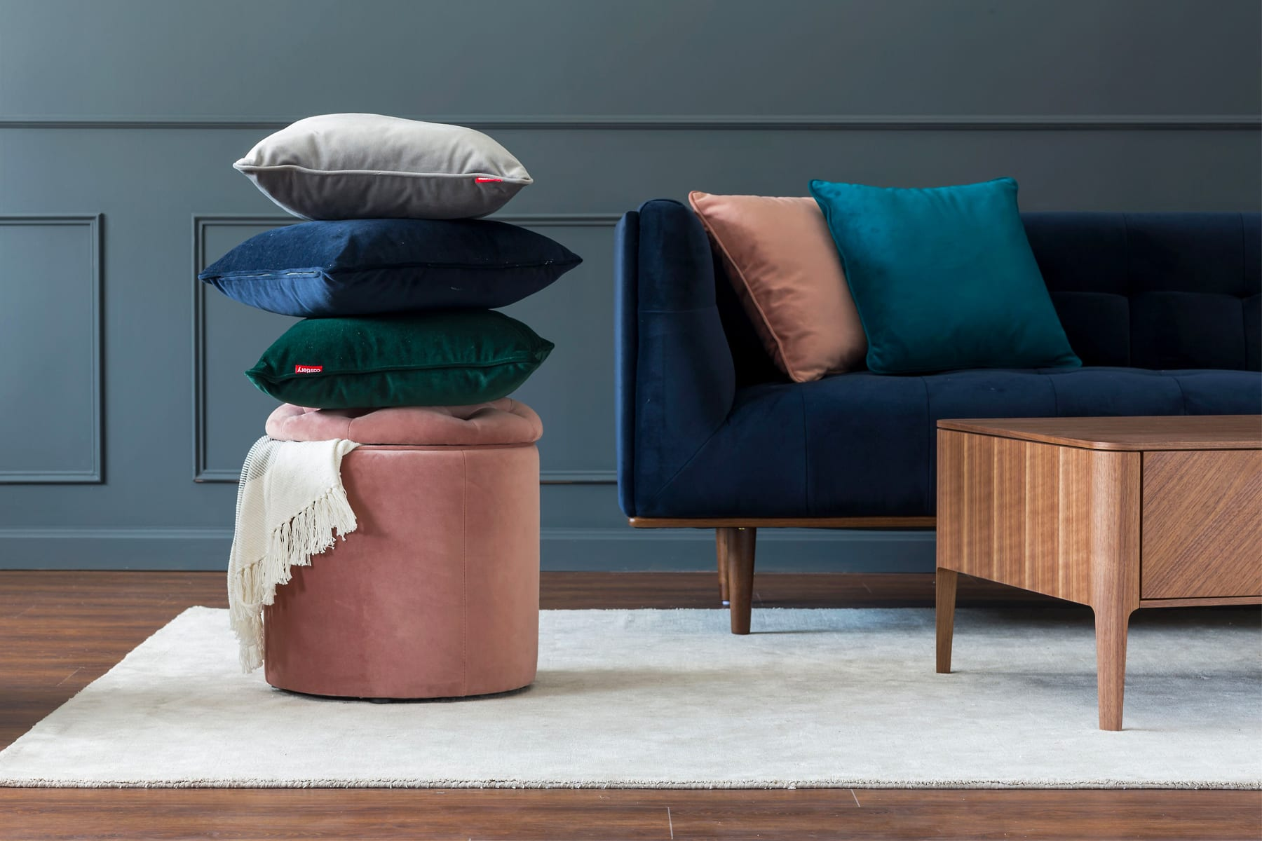 assorted velvet cushions and throw pillows with pink velvet storage stool
