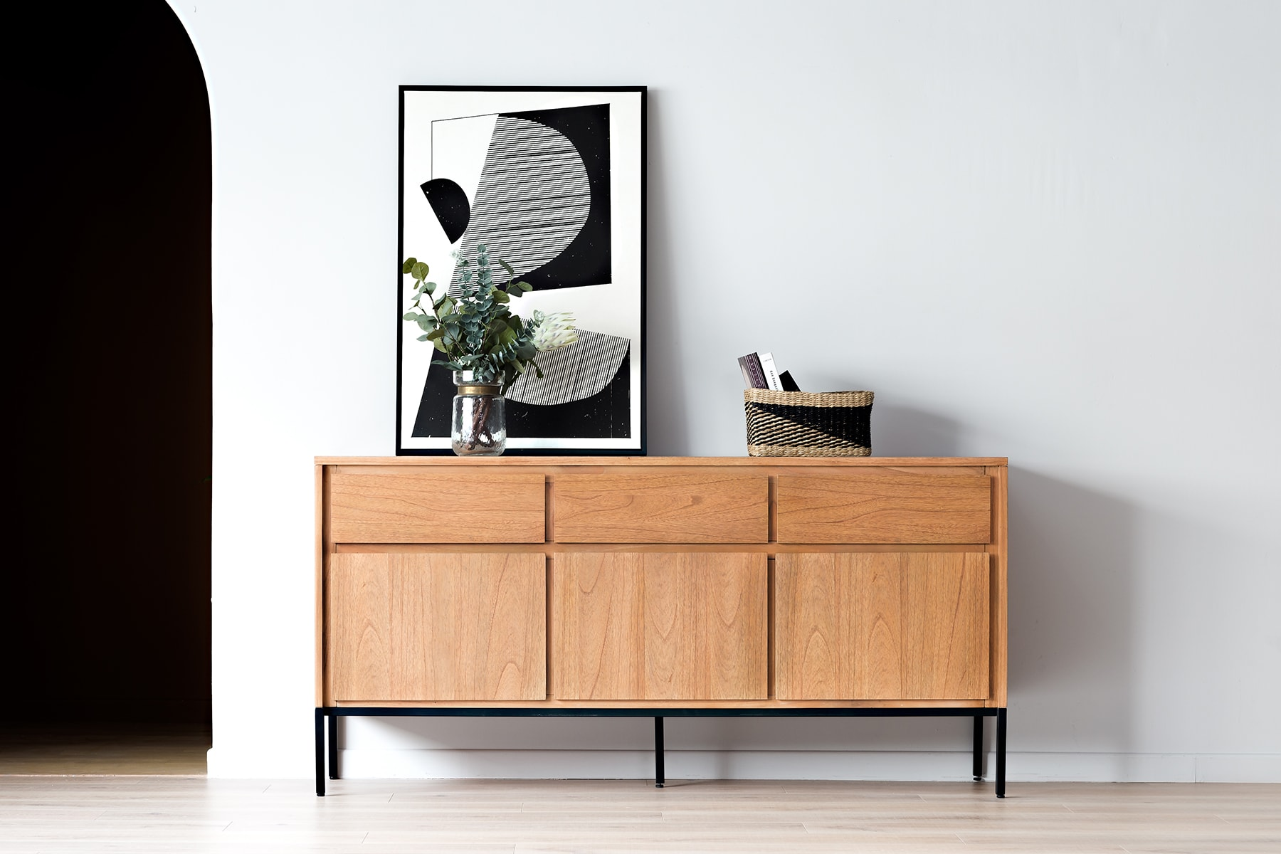 sideboard in walkway with flower vase and framed art