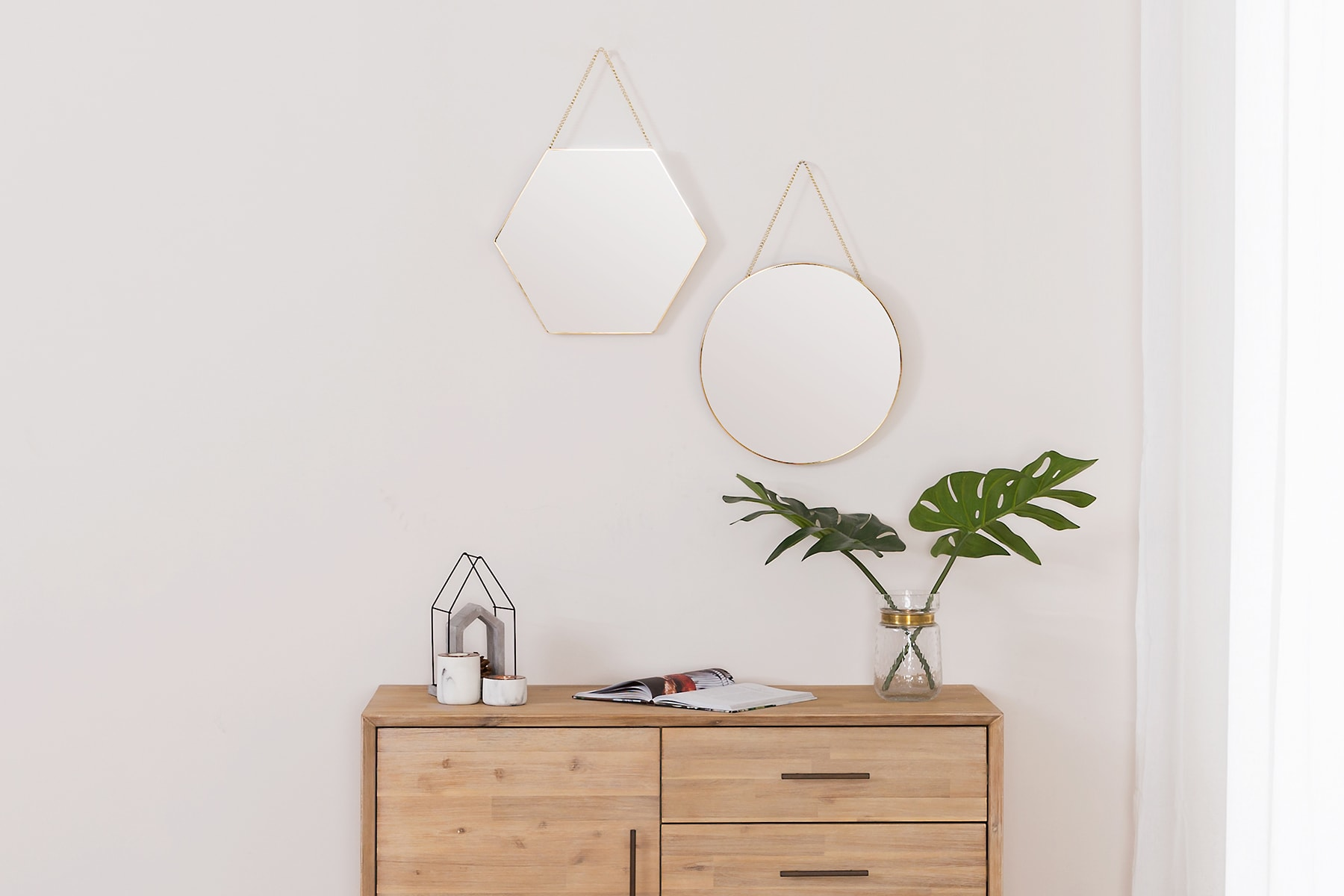 sideboard in walkway with hanging mirrors and plant