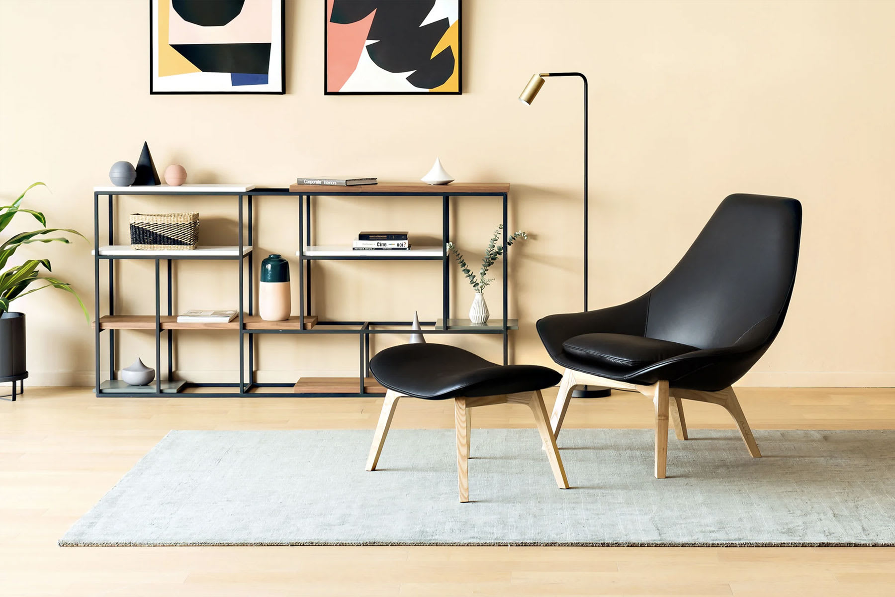 black low leather armchair with ottoman in mid-modern century style