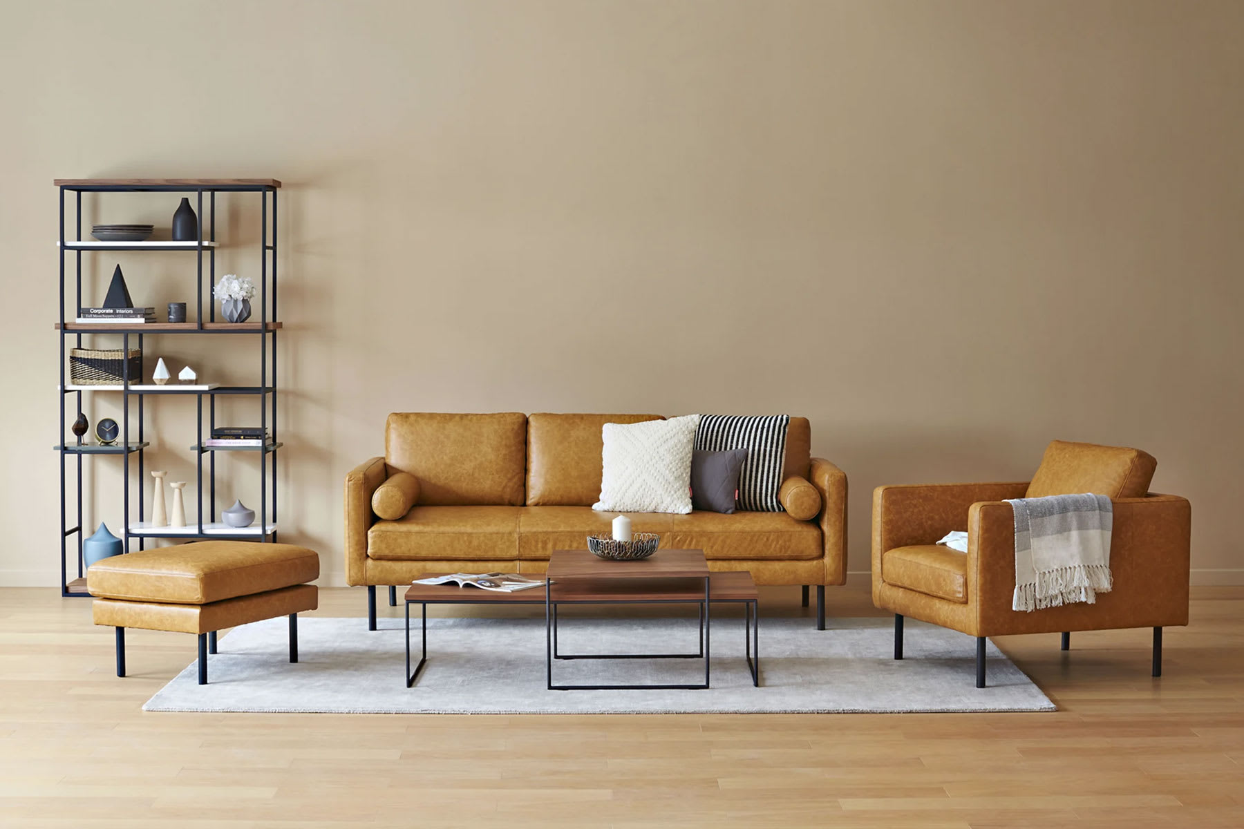 brown leather sofa in living room with armchair, ottoman and coffee table