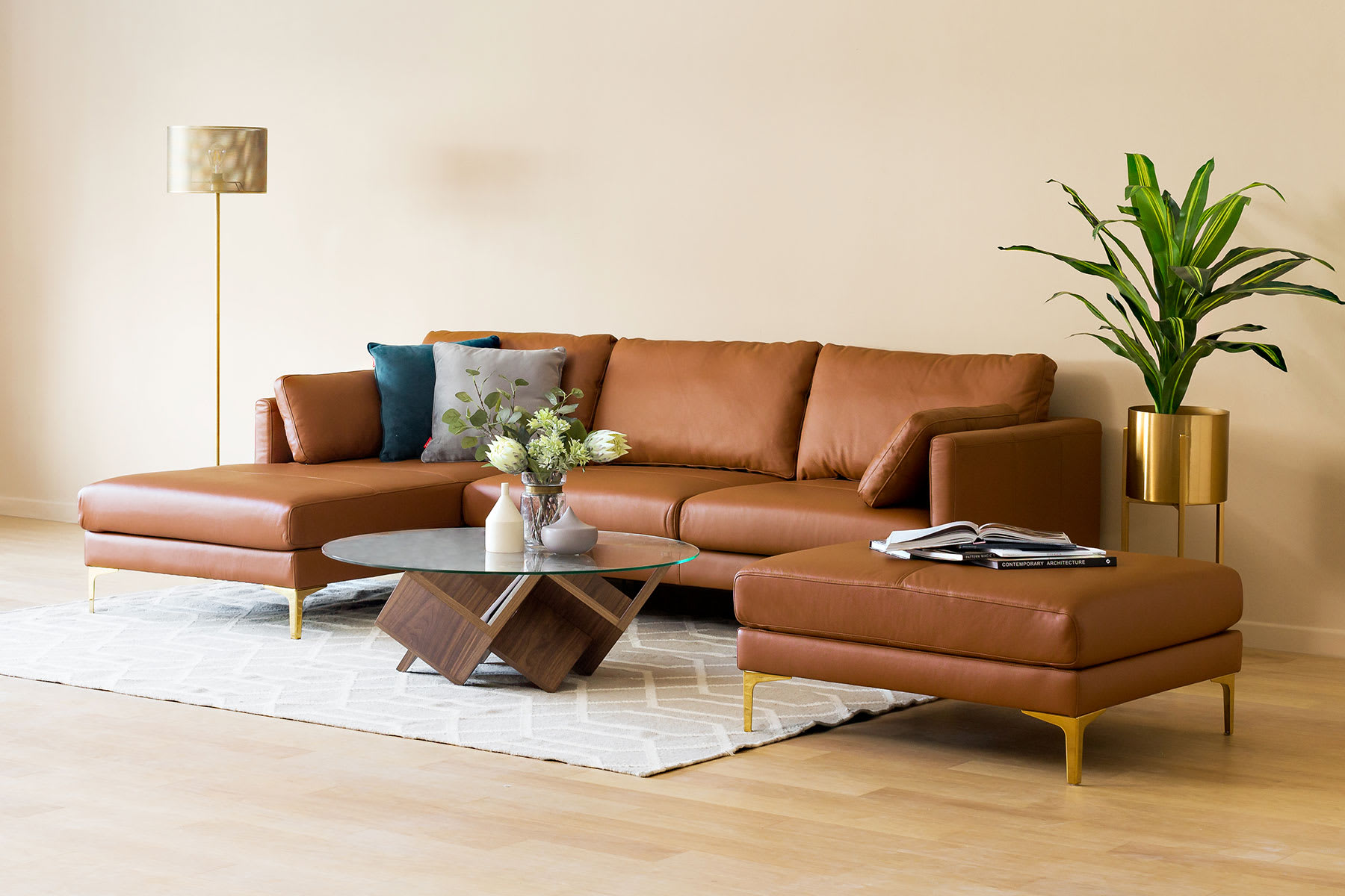 brown sectional leather sofa in living room with ottoman, rug and lamp