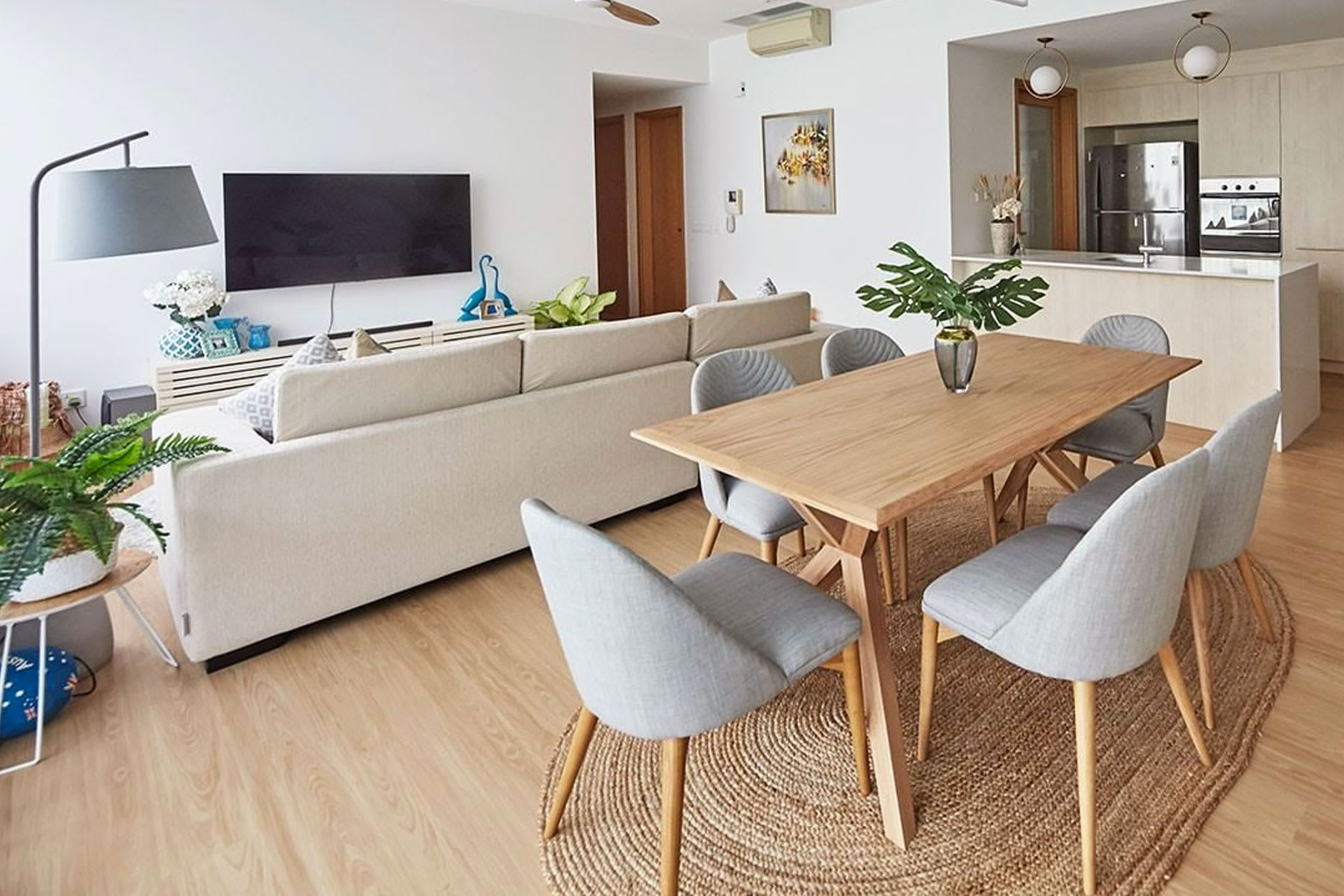 Bright open plan home with dining table, chairs and sofa