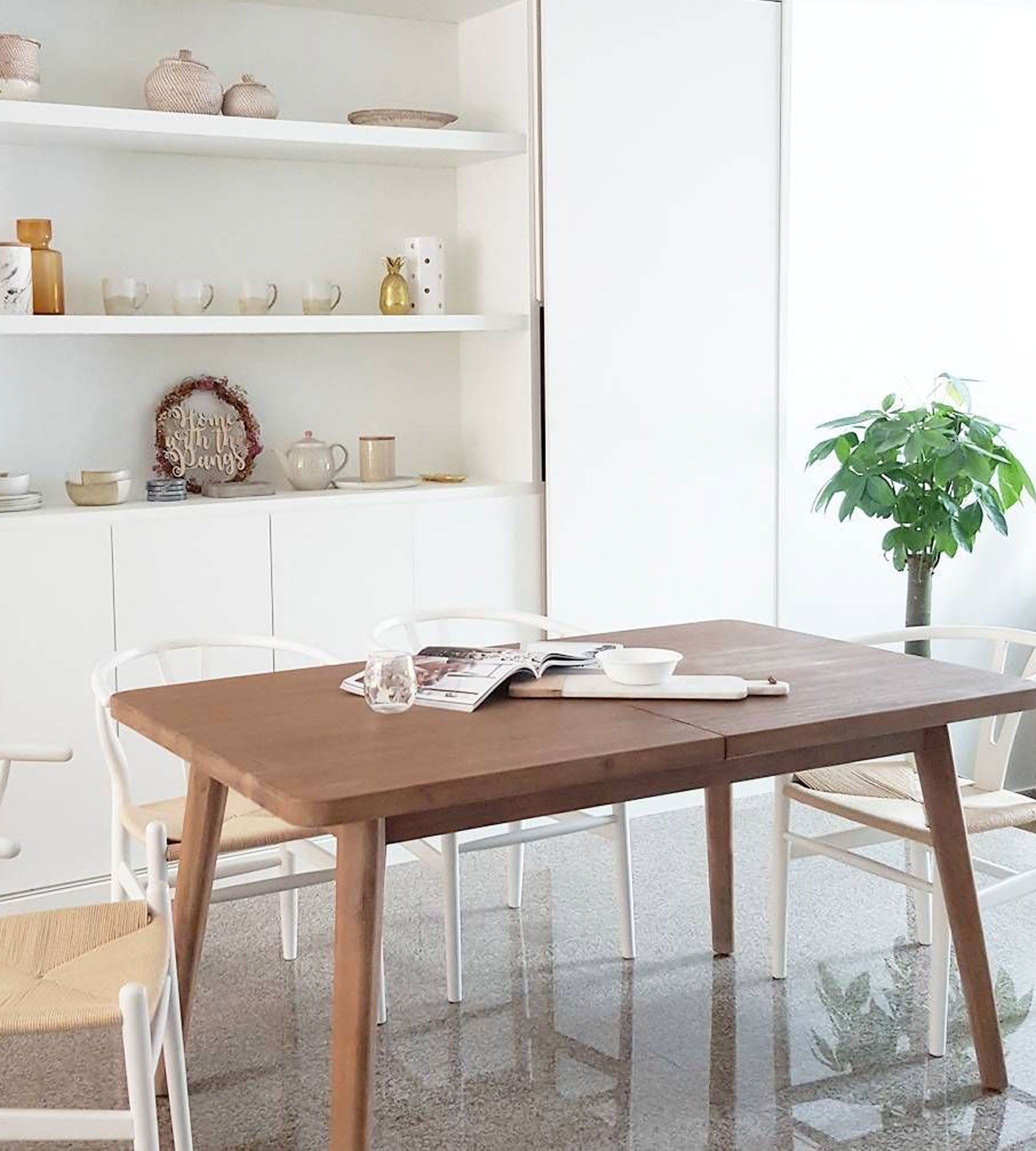 solid wood dining table in modern dining space with chairs and shelf