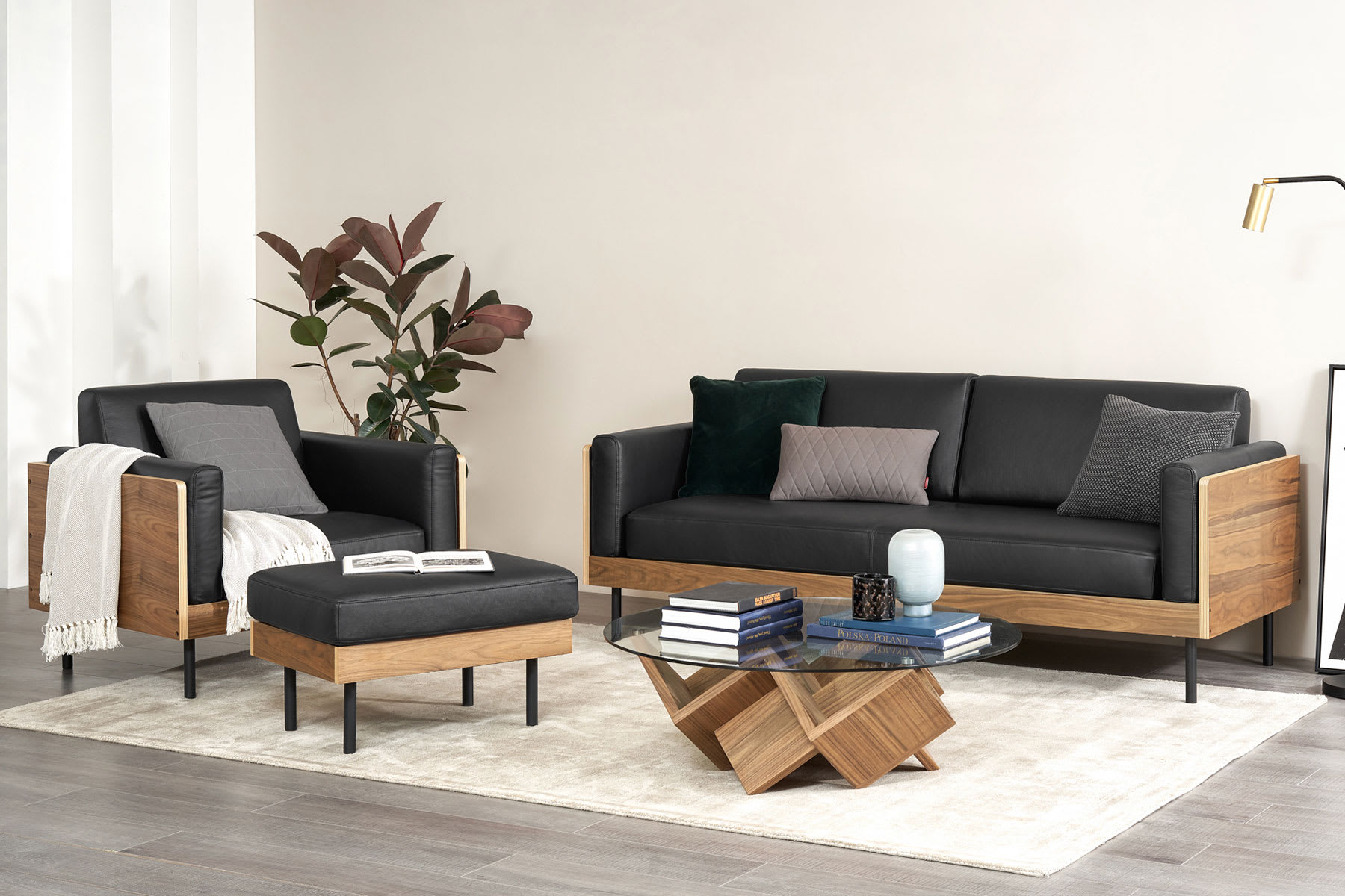 light and airy living room furniture with sofa in black leather, geometric glass coffee table and white floor rug