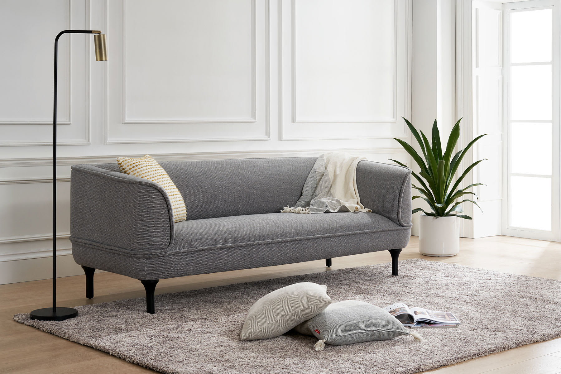 grey sofa in living room with rug, standing lamp, potted plant and cushions