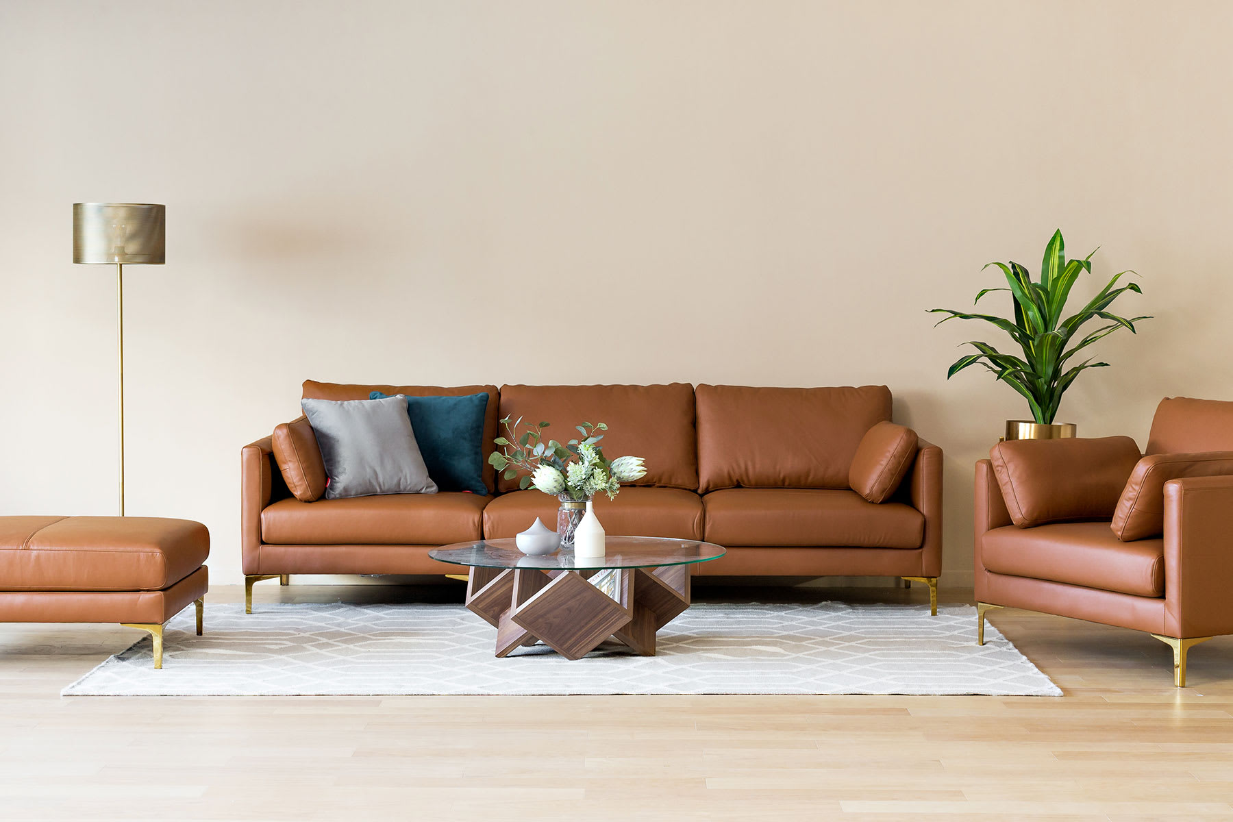 pastel living room with brown top-grain leather sofa in mocha, geometric glass coffee table and brass floor lamp
