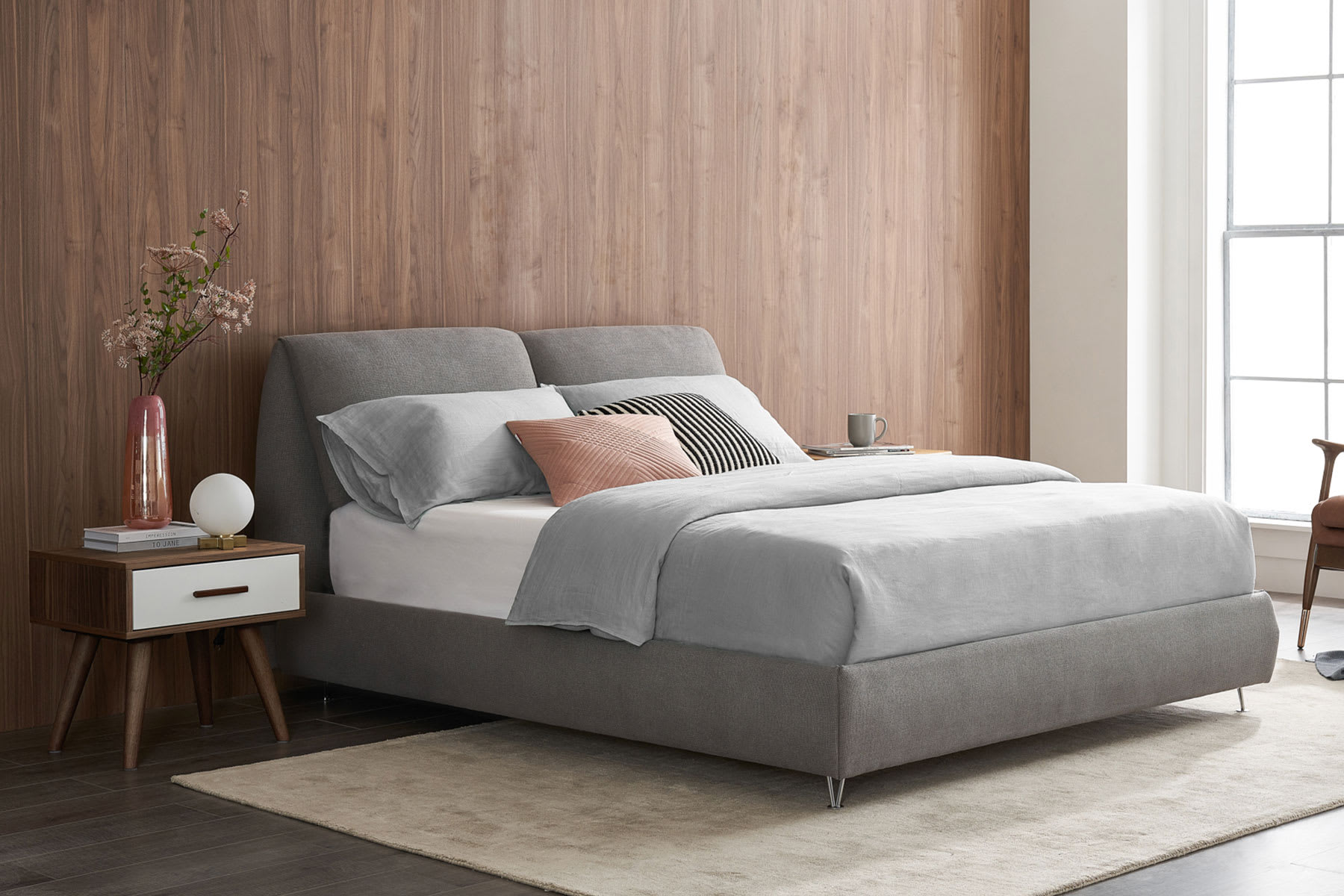light gray upholstered fabric bed with sofa, bedside table and plant