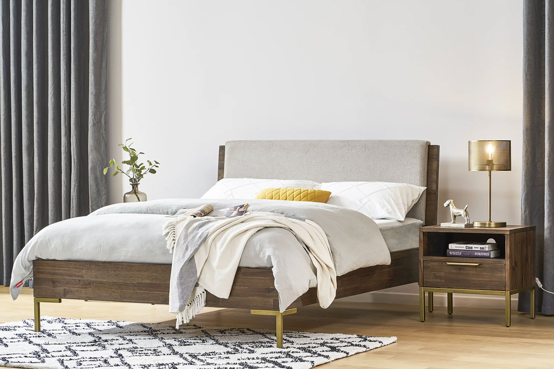 Mid-century modern bed frame with gold legs, bedside table and carpet