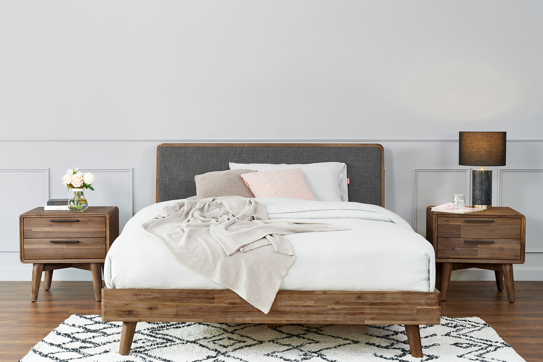 wooden bed with gray fabric headboard, carpet and bedside tables in modern bedroom