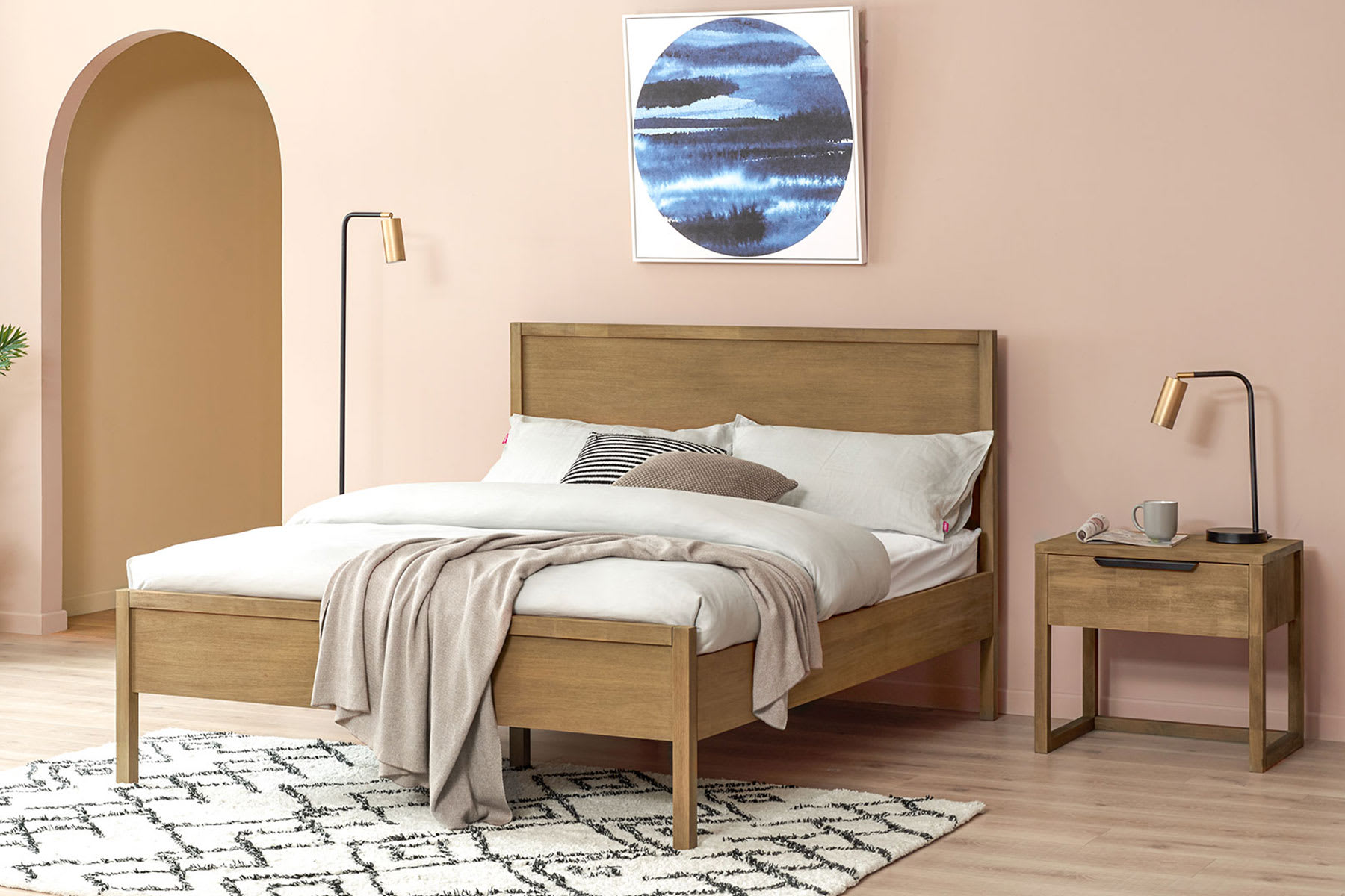 solid mahogany wood bed in pastel bedroom with bedside table and lamp